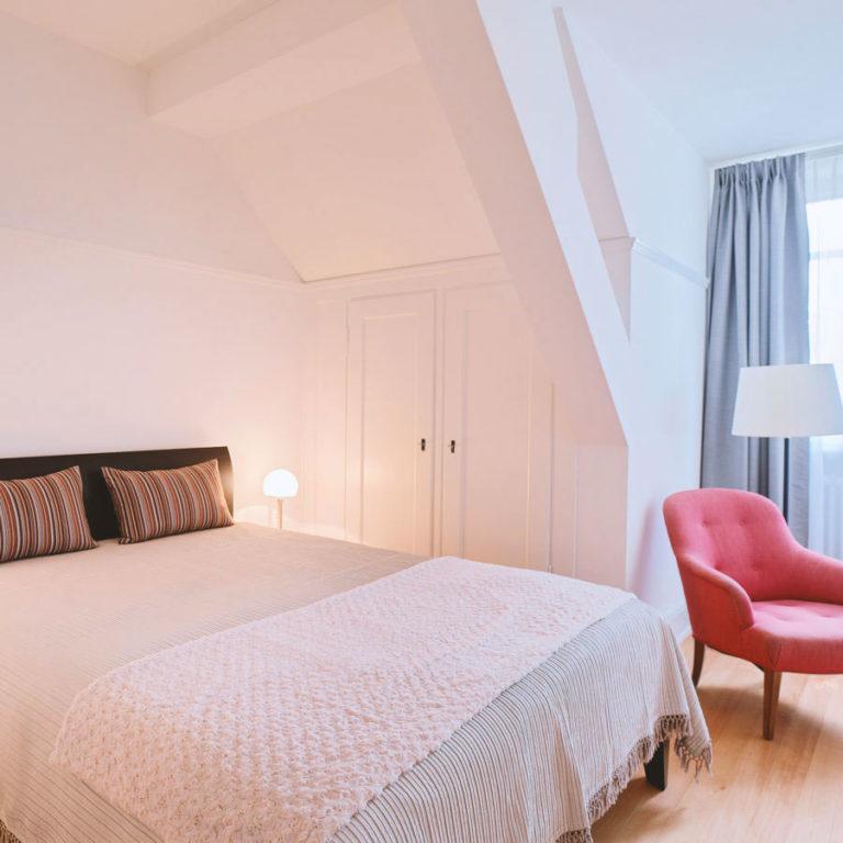 Bequemes Bett und Design Stuhl im Zimmer 10 des Boutique Hotels Signau House & Garden in Zürich